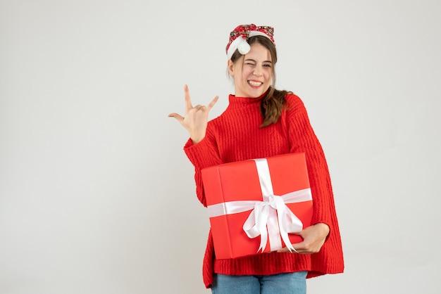화이트에 선물을 들고 바위 기호를 만드는 산타 모자와 함께 행복 한 소녀
