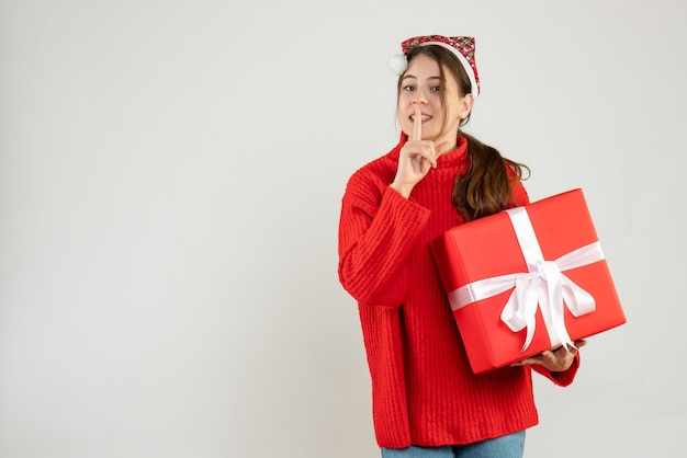 Happy girl with santa hat making shh sign holding gift on white