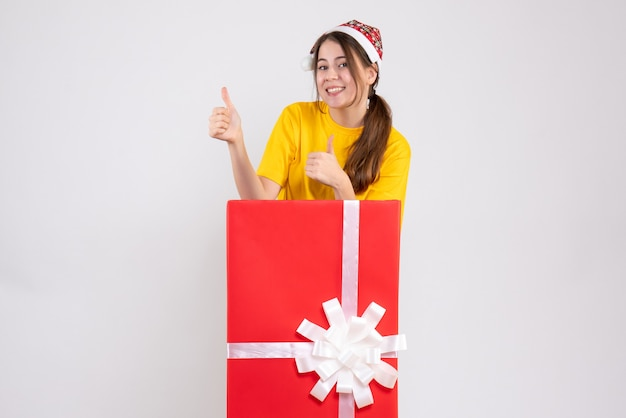 Happy girl with santa hat making thumb up sign standing behind big xmas gift on white