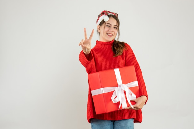 Happy girl with santa hat making victory sign holding gift on white