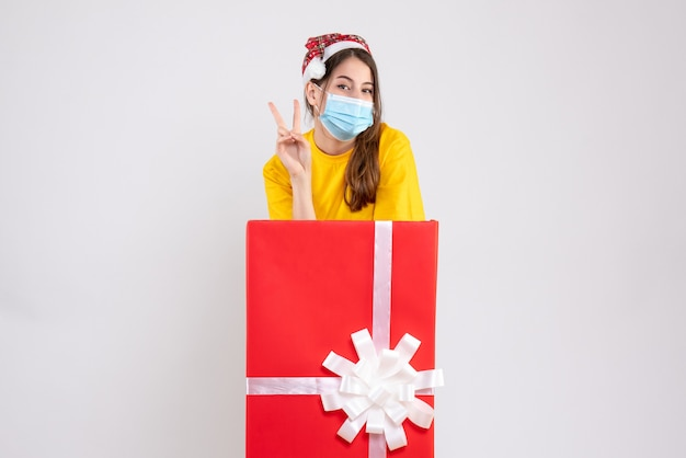 Happy girl with santa hat making victory sign standing behind big xmas gift on white