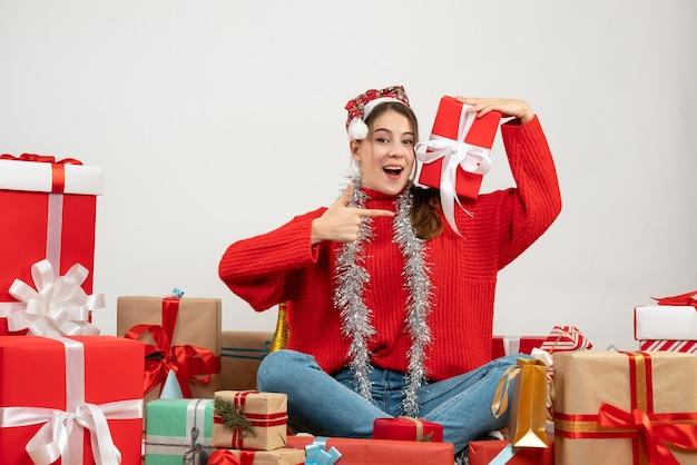 화이트 선물 주위에 앉아 선물을 가리키는 산타 모자와 함께 행복 한 소녀