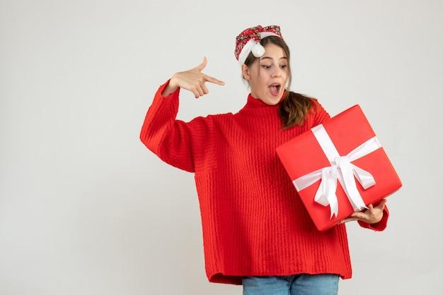 화이트에 그녀의 선물에서 가리키는 산타 모자와 함께 행복 한 여자
