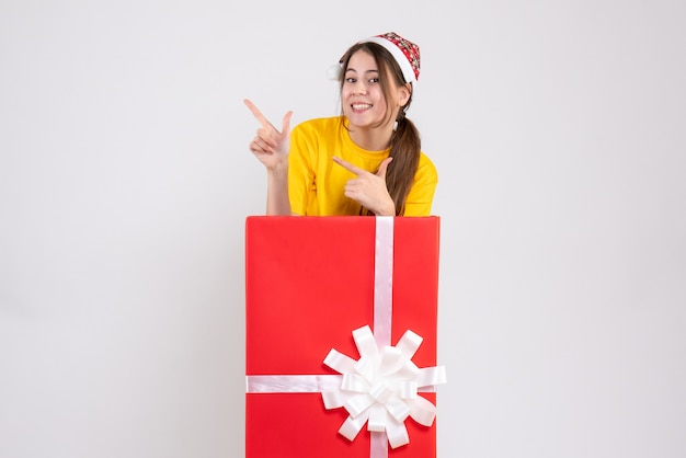 Happy girl with santa hat pointing at something standing behind big xmas gift on white