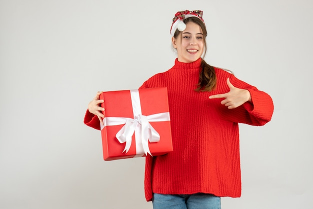 Happy girl with santa hat pointing with finger her gift on white