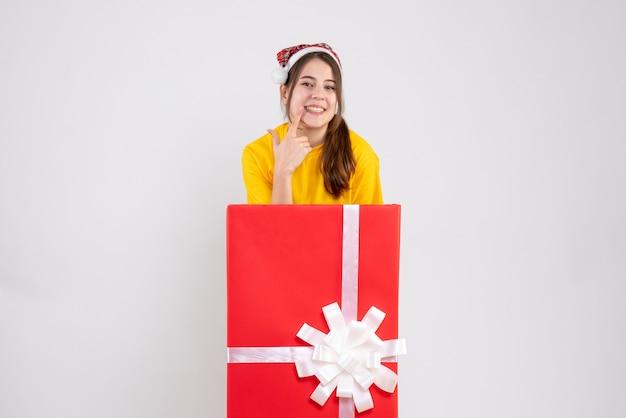 화이트에 큰 크리스마스 선물 뒤에 서있는 그녀의 미소를 보여주는 산타 모자와 함께 행복 한 소녀