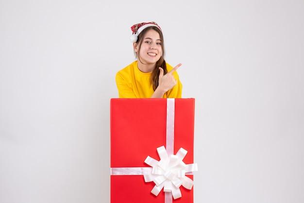 흰색에 큰 크리스마스 선물 뒤에 서 뭔가 보여주는 산타 모자와 함께 행복 한 소녀