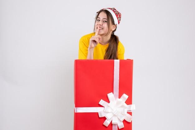 화이트에 큰 크리스마스 선물 뒤에 서있는 산타 모자와 함께 행복 한 소녀