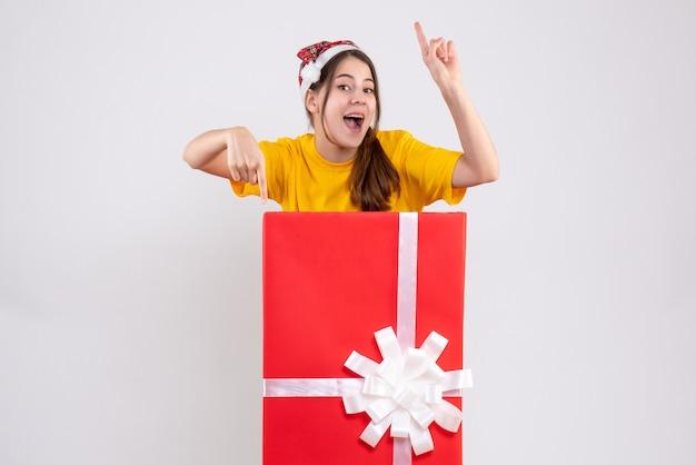 白に存在する大きなクリスマスの後ろに立っているサンタの帽子と幸せな女の子