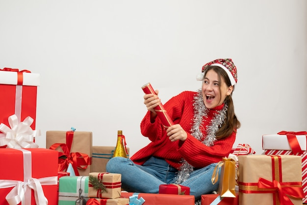 Happy girl with santa hat using party popper sitting around presents on white