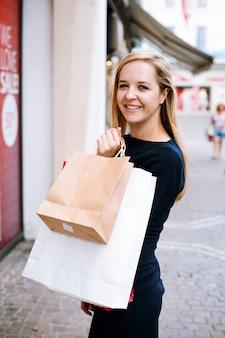 Счастливая девушка с сумками смотрит в камеру