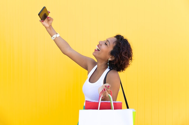 Счастливая девушка с хозяйственными сумками делает селфи на своем телефоне на желтой стене.