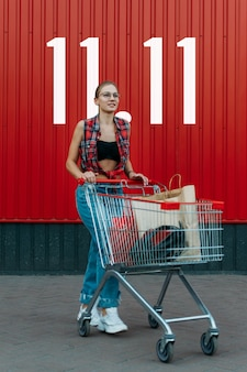 Happy girl with shopping cart on red wall shop background with 11.11 day number