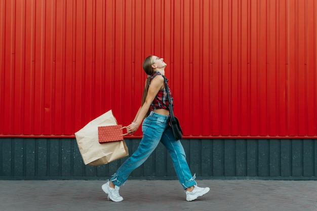 Happy girl with shopping paper bag on red wall shop background young woman holding shopping bag full