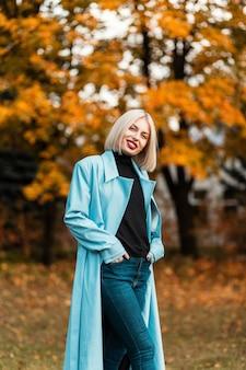 秋の黄金の公園を歩いているファッショナブルな長い青いコートの短い髪と赤い唇を持つ幸せな女の子