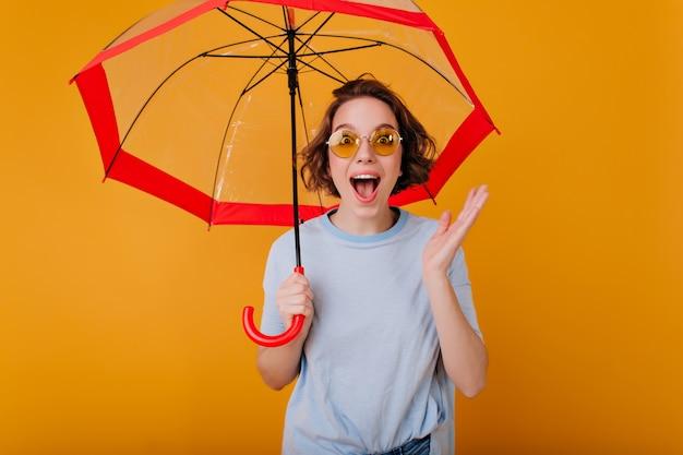 傘の下で笑いながらポーズをとる短い髪型の幸せな女の子。黄色の壁に日傘を持っている流行のセーターで魅惑的な白人女性のスタジオショット。