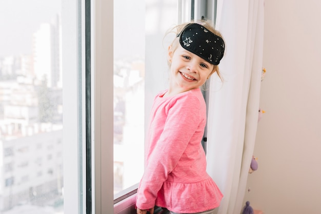 Happy girl with sleeping eye mask standing near glass window