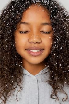 雪と幸せな女の子のクローズアップ