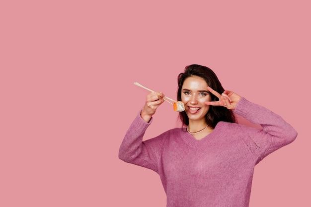 분홍색 배경에 스시와 함께 행복 한 여자