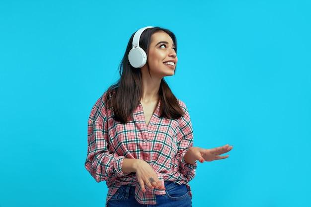 Счастливая девушка с белыми наушниками слушает музыку и танцует на синем