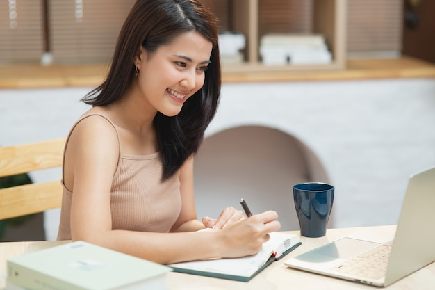 Happy girl writing on notebook look at laptop screen listen and learning online courses at apartment