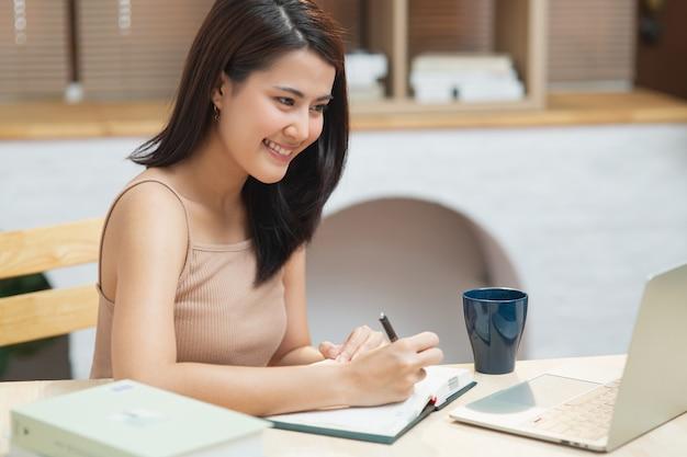 노트북 화면을 보고 노트북으로 글을 쓰는 행복한 소녀는 아파트에서 온라인 과정을 듣고 학습합니다.