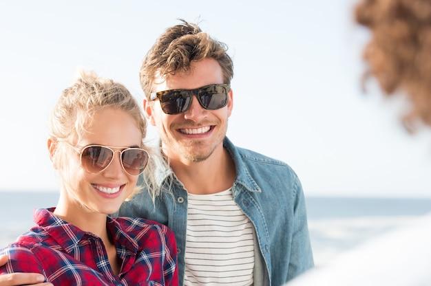 幸せなガールフレンドとボーイフレンドは、日没時にサングラスをかけて楽しんでいます