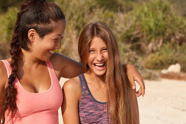 행복한 여자 친구가 해변을 산책하면서 껴안고, 긍정적으로 웃으며, 즐거운 순간을 즐기고, 열대 지방에서 휴식을 취합니다.