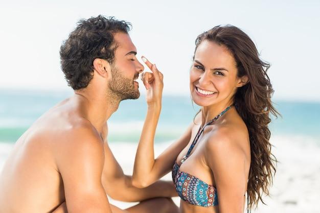 Счастливая девушка кладет солнцезащитный крем на нос парня