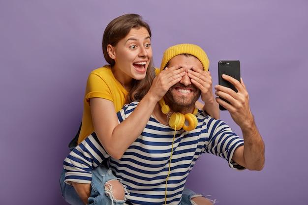 幸せなガールフレンドはピギーバックに乗って、彼氏が目を覆って楽しんで、驚きを準備します。陽気なヒップスターがスマートフォンを前に持っている