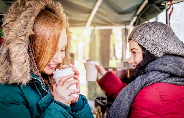 Happy girlfriends best friends sharing time together with coffee takeaway cup in autumn season