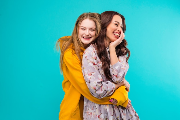 Happy girlfriends holding each other isolated over turquoise blue background