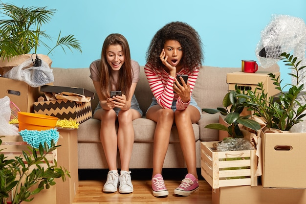 Happy girlfriends sitting on the couch surrounded by boxes