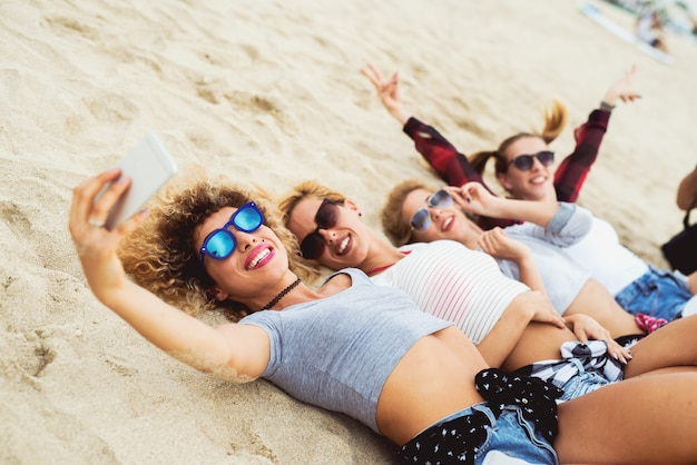 Happy girlfriends taking selfies lying on sand. trendy summer outfit.