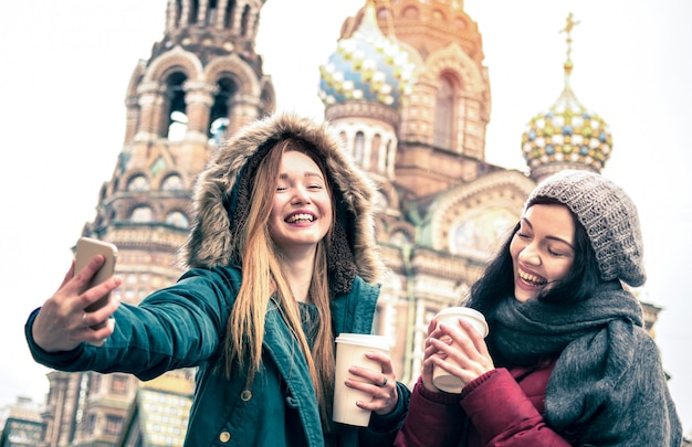 Happy girlfriends taking winter selfie in saint petersburg