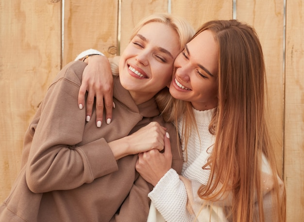 Happy girlfriends in warm clothes hugging together
