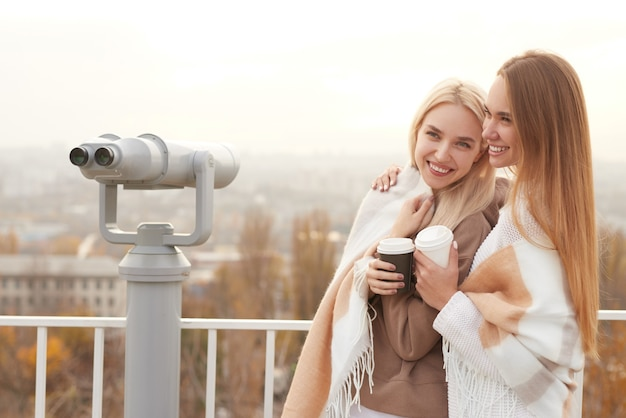 Happy girlfriends with coffee standing on observation deck