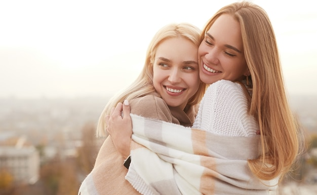 Happy girlfriends with warm scarf hugging in cold day