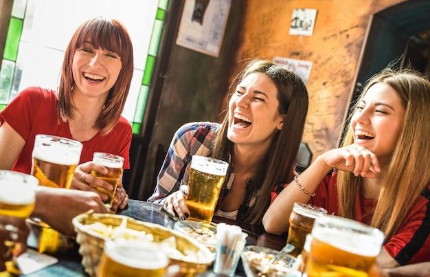 幸せなガールフレンドの女性グループが醸造所のバーのレストランでビールを飲む