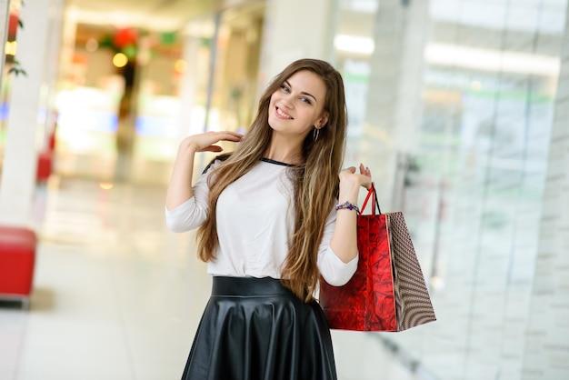幸せな女の子がモールで買い物をしています。