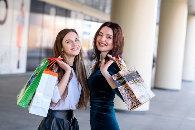 Счастливые девушки делают покупки в торговом центре