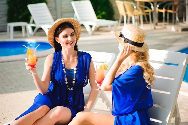 素晴らしい休日の幸せな女の子の親友、プールの近くでカクテルを飲み、楽しんでいます