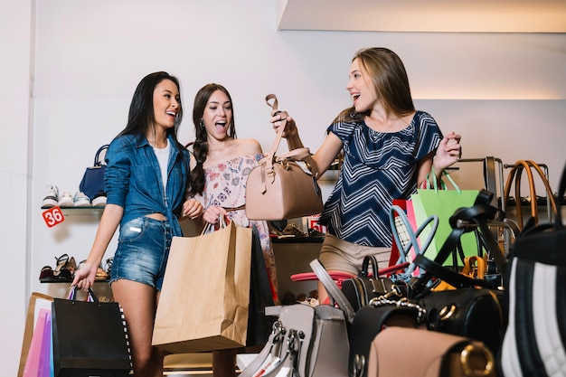 Happy girls choosing handbags in shop
