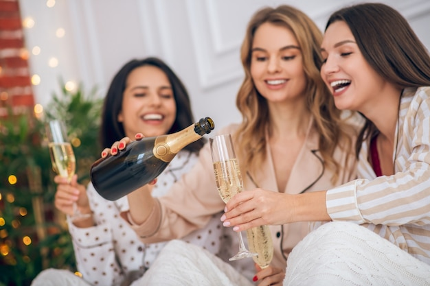 Happy girls. cute girls drinking champagne and looking happy