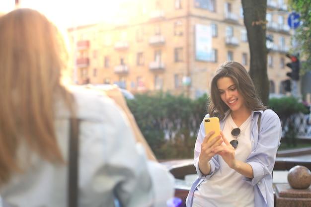 幸せな女の子の友達が街でお互いに写真を撮っています。