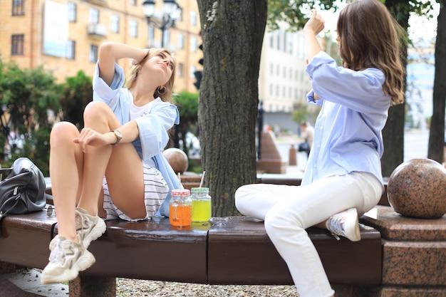 幸せな女の子の友達が街のベンチでお互いに写真を撮っています。