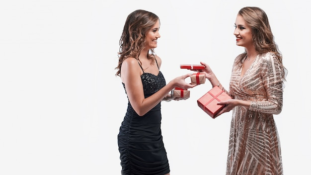 Happy girls friends exchanging presents isolated on white