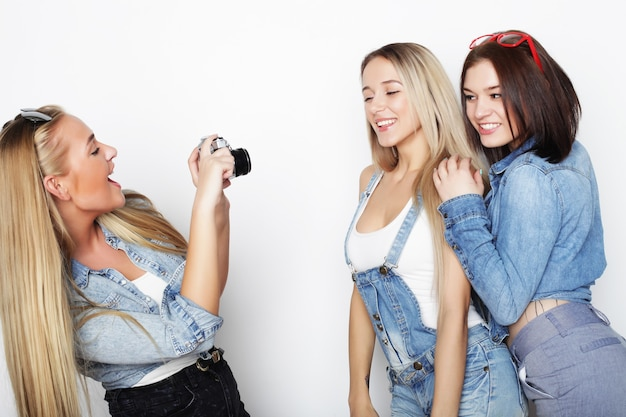 白い壁を越えてカメラで写真を撮る幸せな女の子の友達