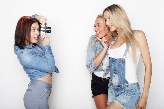 カメラで写真を撮る幸せな女の子の友達