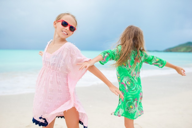 Happy girls having fun and enjoying vacation on tropical beach with white sand and turquoise ocean water